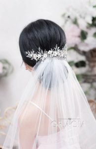 neat low chignon with pin and veil