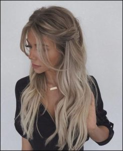 wavy half up loose hairstyle with middle part